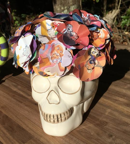 Coco little golden book hand-cut paper flower arrangement in Skull vase.