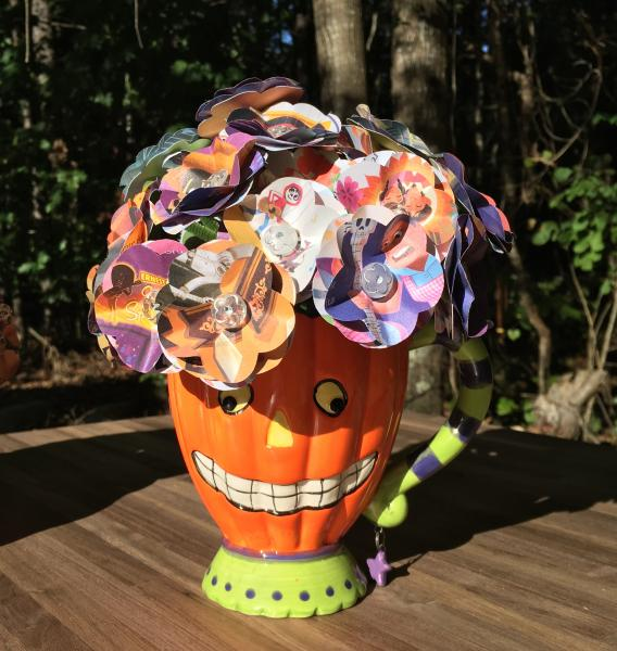 Coco little golden book hand-cut paper flower arrangement in smiling pumpkin mug