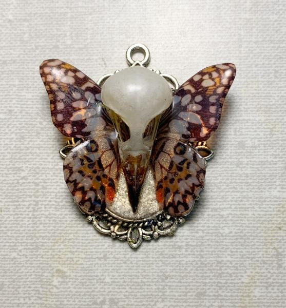 Butterfly and bird skull pendant